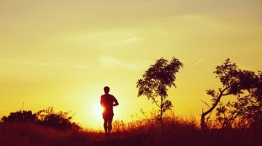 Picture of young man running at the sunset - back lit