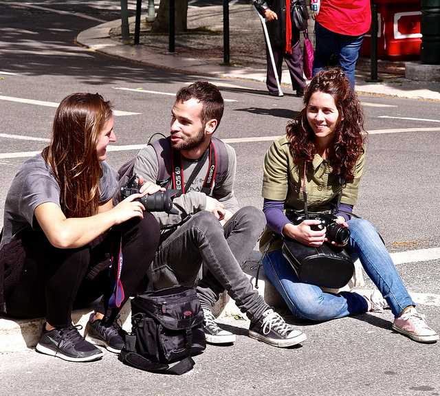 Picture by Pedro Ribeiro Simões. Three photographers in their mid-twenties sitting on the curb, chatting and smiling. A male in the middle of two girls.